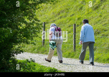 Elderly female friends struggling to walk up a hill in the countryside. - Stock Photo