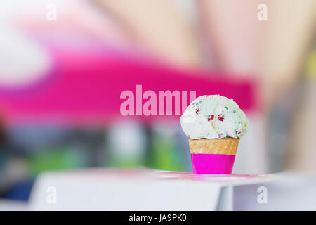 Vanilla ice cream in waffle cone topped with colorful sprinkles, bright blurry background. Selective focus. Copy - Stock Photo