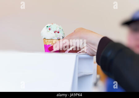 Close-up of Woman's hand takes Delicious Vanilla ice cream in waffle cone topped with colorful sprinkles. Selective - Stock Photo