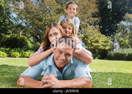 Happy family members lying on each other in the park smiling at camera - Stock Photo