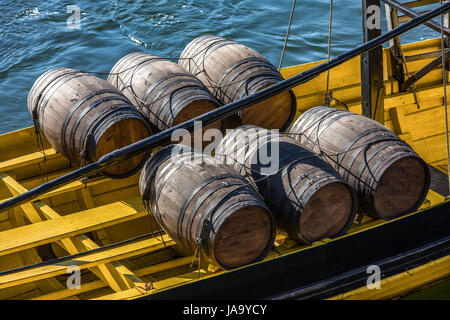 Wine barrels on the ship in Porto, Portugal. Traditional wine transport on the river Douro. - Stock Photo