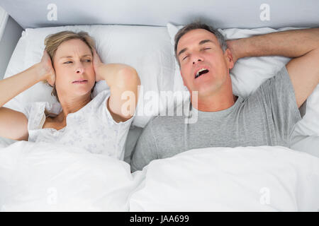 Annoyed wife blocking her ears from noise of husband snoring in bedroom  at home   Stock. Wife blocking her ears from noise of husband snoring Stock Photo