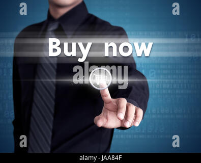 Business man pressing buy now on shopping cart icon - Stock Photo