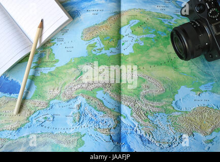 Ready for the Holidays! Lined Note Papers with White Pencil and a Black Camera on the World Map - Stock Photo