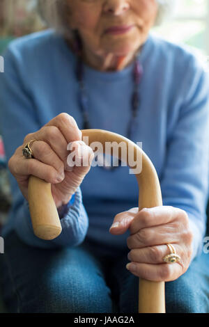 Close Up Of Senior Woman Sitting In Chair Holding Walking Cane - Stock Photo