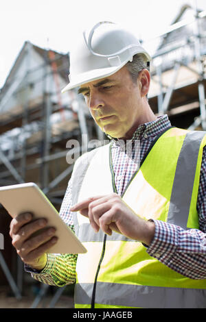 Architect On Building Site Using Digital Tablet - Stock Photo