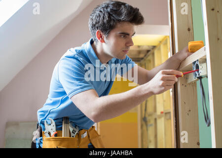 Electrician Installing Socket In New House - Stock Photo