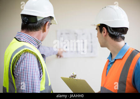 Rear View Of Architect On Site Discussing Plans With Builder - Stock Photo