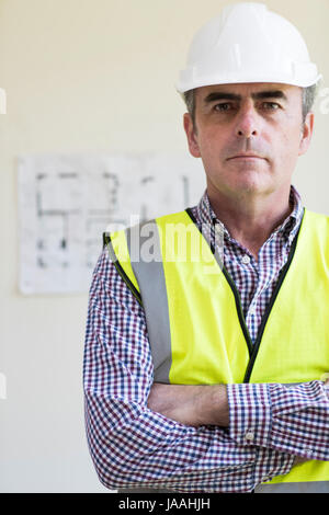 Portrait Of Architect Wearing Hard Hat With Plans In Background - Stock Photo