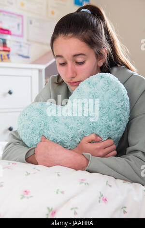 Young Girl Lying On Bed Hugging Heart Shaped Cushion - Stock Photo