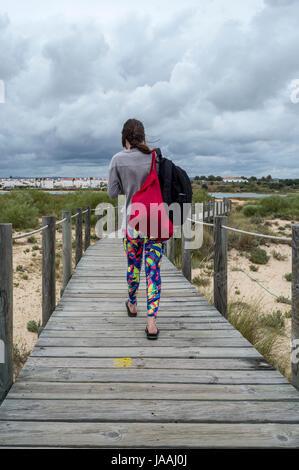 woman tourist walking along wooden boarwalk on Praia de Cabanas, Portugal - Stock Photo