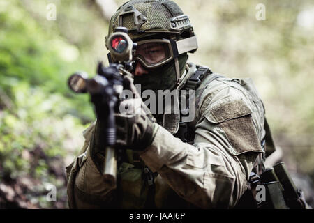 Photo of sniper in woods - Stock Photo