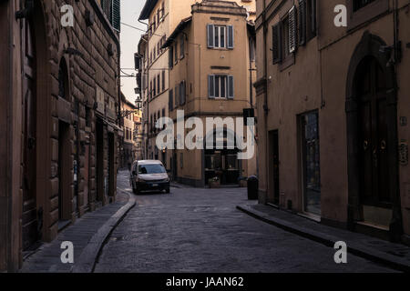 Narrow street and buildings with parked white van in Florence Italy, at dawn. - Stock Photo