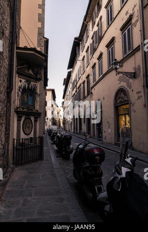 Narrow street and buildings with parked scooters in Florence Italy, at dawn. - Stock Photo