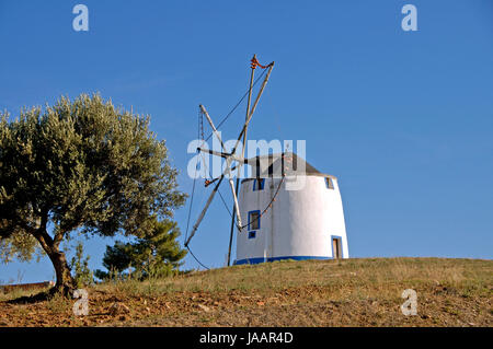 An old traditional windmill standing on top of a hill in Portugal. - Stock Photo