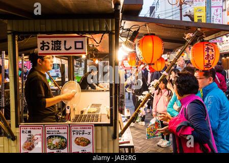 Japan, Osaka, Dotonbori. Night time. People at take away food counter, selling fried Japanese traditional food. - Stock Photo