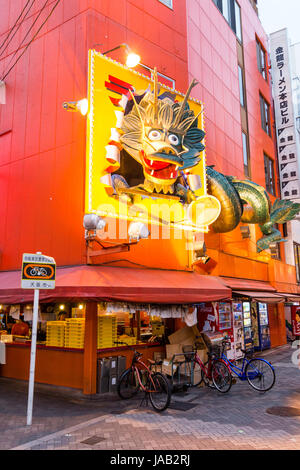 Japan, Osaka, Dotonbori. Night time. Kinryu Ramen takeaway counter and resturant with large iconic floating dragon - Stock Photo