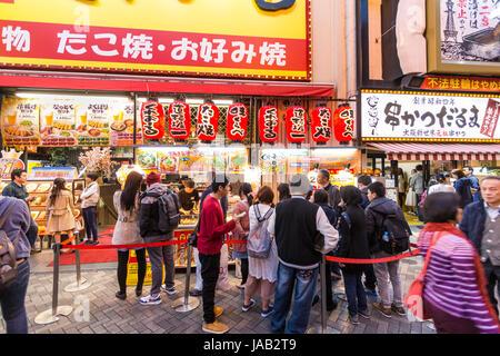 Dotonbori, Osaka. People queuing up to buy traditional Japanese food,  Takoyaki and Okonomiyaki from take-away counter - Stock Photo