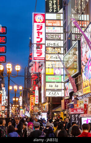 View along main street in Dotonbori, the pleasure and entertainment centre of Osaka at Night time. Illuminated signs - Stock Photo