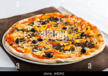 A pizza with peppers, mozzarella, tomatoes, olives cooked in wood fires and served in a restaurant on a white plate. - Stock Photo
