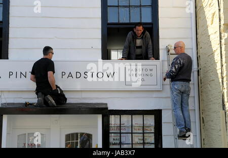 Padstow, Cornwall, UK - April 6th 2017: Workmen fitting a new sign to the 'A Pint of Padstow' brewery shop - Stock Photo