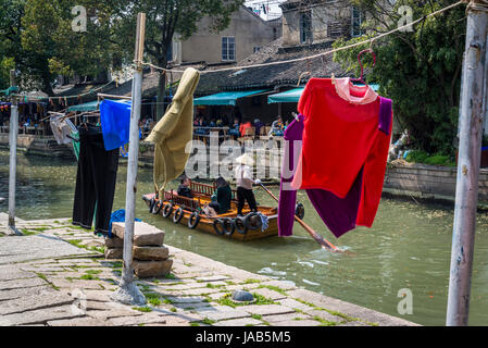 Person rowing a boat on a canal and washing drying in the street, Ancient water town of Tongli, Suzhou, Jiangsu - Stock Photo