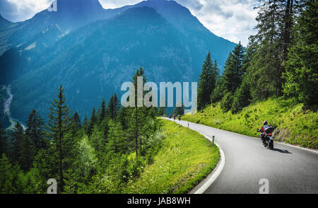 Motorcyclists in mountainous touring, extreme adventure, European journey, extreme road along Alps, active holiday - Stock Photo
