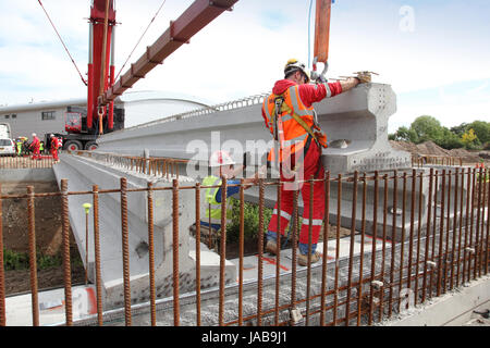 Workmen guide a large, pre-cast concrete beam into place for the construction of a new road bridge in Woking, Surrey, - Stock Photo