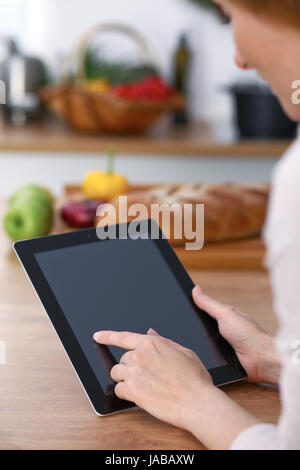 Haman hands  using touch pad in the kitchen. Closeup of woman making online shopping by tablet computer and credit - Stock Photo