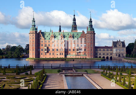 Frederiksborg Castle in Dutch Renaissance style and the Baroque Garden. Hillerød near Copenhagen. Morning sun, clouds - Stock Photo