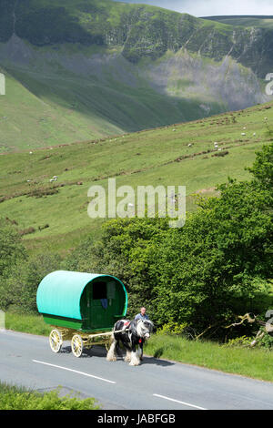 Gypsy travellers with horse drawn caravan on the A683 near Cautley, Cumbria, UK. - Stock Photo