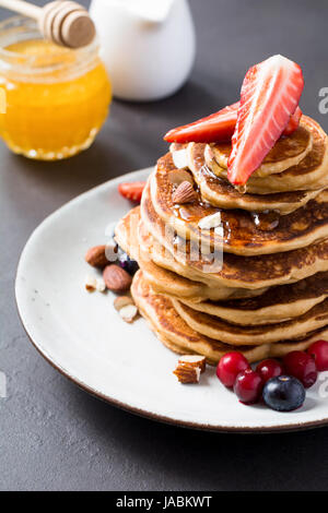 Stack of pancakes with fresh berries and honey syrup on white plate closeup view - Stock Photo