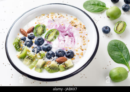 Smoothie bowl with acai berry, kiwi, blueberry, almond, coconut, bee pollen and baby spinach on white background. - Stock Photo