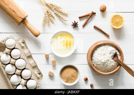 Baking ingredients on white wooden table. Eggs, brown sugar, white flour, wheat ears, spices, nuts and lemon on - Stock Photo