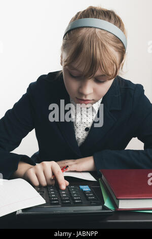 School girl using calculator, closeup portrait over white wall background - Stock Photo