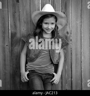 Children girl as kid cowboy girl cowgirl posing on wooden fence far west style - Stock Photo