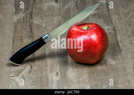 The knife cuts a red apple lying on a wooden surface - Stock Photo