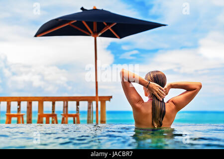 Young happy woman have fun in outdoor infinity pool with view to ocean surf. Positive girl swim, relax at poolside. - Stock Photo