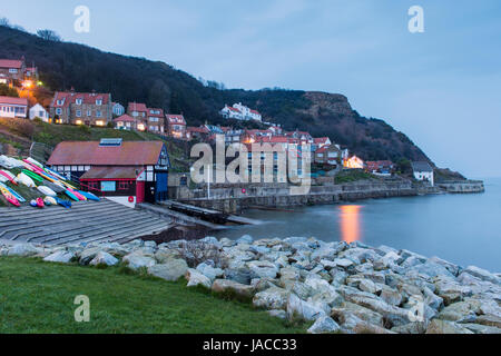 Lights are lit in houses in evening view of pretty quaint coastal village, with cliffs, boats & calm sea - Runswick - Stock Photo