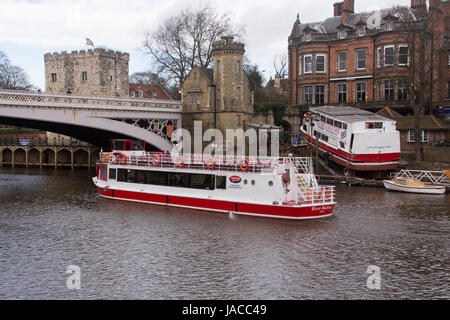 2 pleasure boats - 1 sailing past the other, out of  water on slipway, being repaired & refurbished, 1 man working - Stock Photo