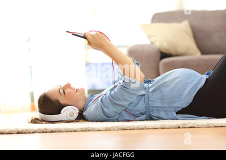 Side view of a pregnant woman listening music with headphones and a smart phone lying on the floor at home - Stock Photo