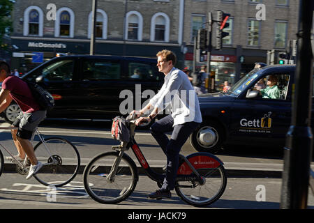 Man riding a Santander electric hire bike cycling through Kings Cross, London, in the rush hour - Stock Photo