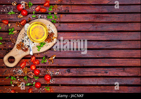 Food background with copy space. Spices, cherry tomatoes, basil and vegetable oil on dark wooden table, top view - Stock Photo