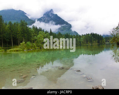 Mountain peaks shrouded in cloud and mist surrounded by evergreen forests in Austria - Stock Photo