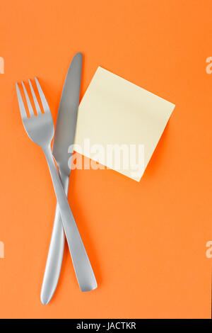 Fork and knife with note paper on orange background. Template and background - Stock Photo