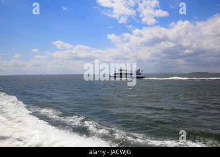 NYC Ferry cruising through the Lower New York Bay - Stock Photo