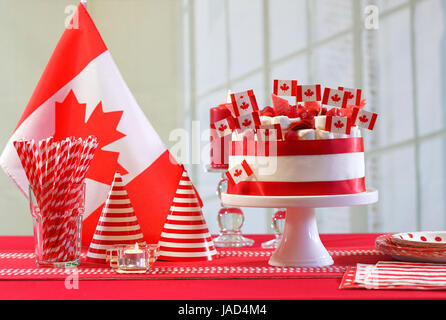 Canada Day national holiday celebration party table with showstopper cake and flags. - Stock Photo