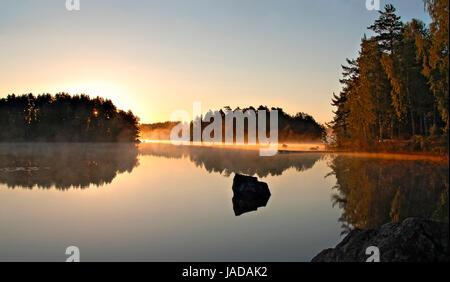 Leichter Nebel leuchtet goldfarben in der Morgensonne  an einem spiegelglatten schwedischen See; light fog glows - Stock Photo