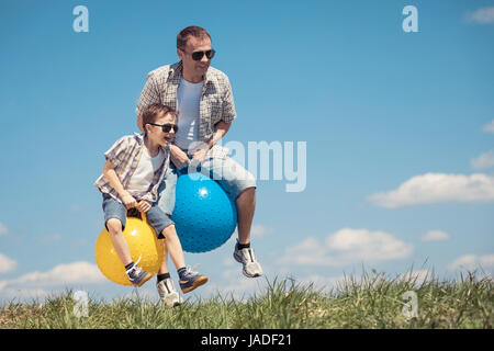 Father and son playing on the field at the day time. People having fun outdoors. They jumping on inflatable balls - Stock Photo
