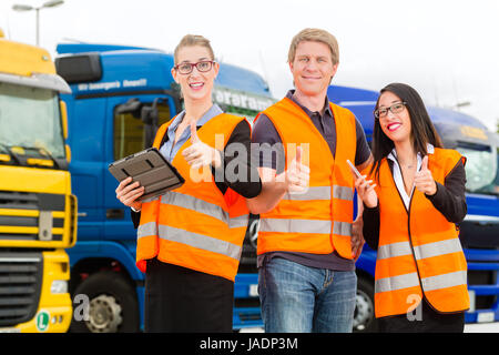 Logistics - proud driver or forwarder and colleagues with tablet computer, in front of trucks and trailers, on a - Stock Photo